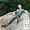 A photo of a statue of Oscar Wilde in Merrion Square. In the statue he is reclining on a large rock.